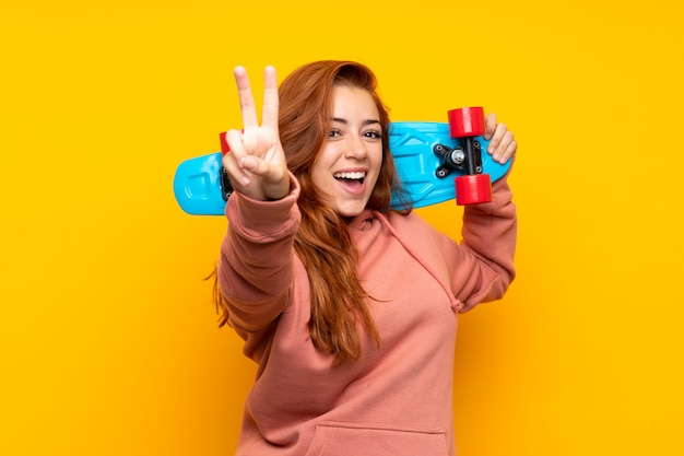 Teenager redhead girl with skate making victory gesture over isolated yellow wall