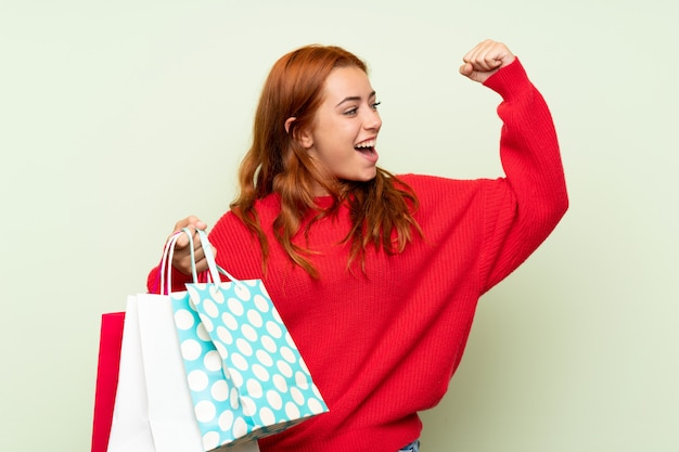 Teenager redhead girl with sweater over isolated green background holding a lot of shopping bags