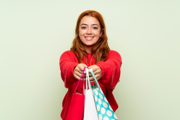 Teenager redhead girl with sweater over isolated green  holding a lot of shopping bags
