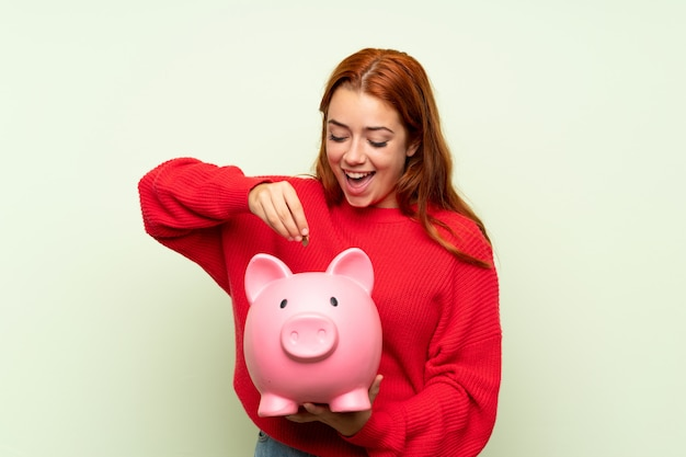 Teenager redhead girl with sweater over isolated green wall holding a big piggybank