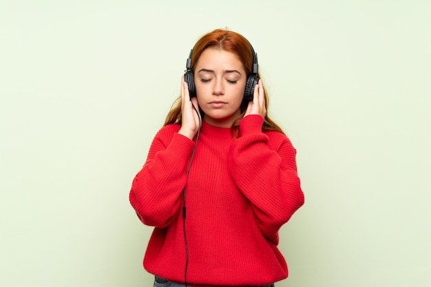 Teenager redhead girl with sweater over isolated green wall listening to music with headphones