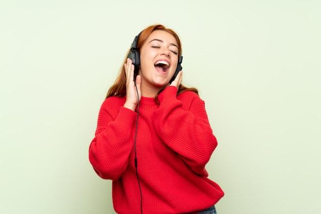 Рыжая девушка-подросток со свитером над изолированным зеленым, слушая музыку в наушниках