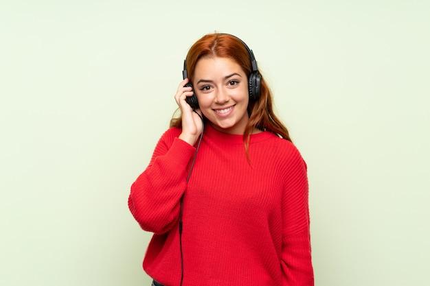 Рыжая девушка-подросток со свитером над зеленым, слушая музыку в наушниках