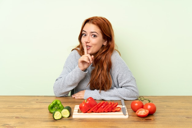 Teenager redhead girl with vegetables in a table doing silence gesture