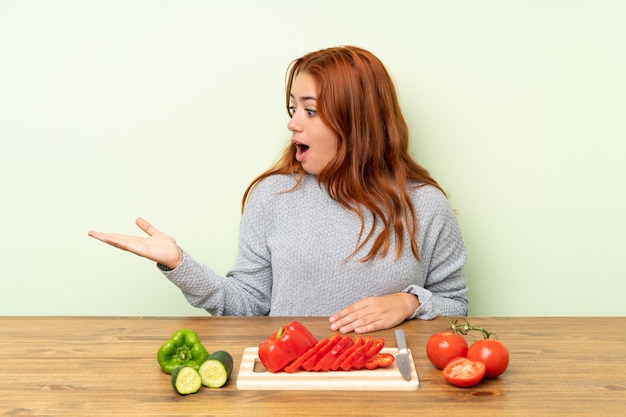 Teenager redhead girl with vegetables in a table holding copyspace imaginary on the palm