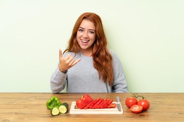 Teenager redhead girl with vegetables in a table making phone gesture