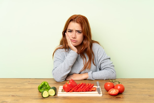 Teenager redhead girl with vegetables in a table unhappy and frustrated