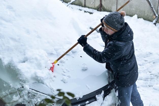 Подросток убирает снег с машины лопатой зимой