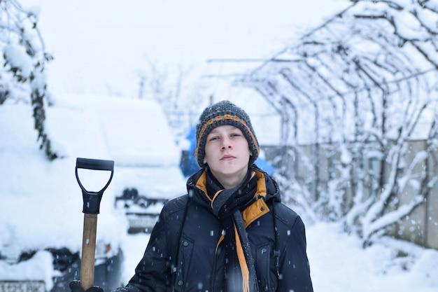 Подросток убирает снег лопатой зимой
