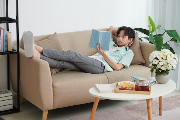 Teenager resting on sofa, drinking tea and reading interesting book with novels