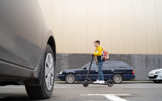 10代の若者が街の通りを電動スクーターに乗る