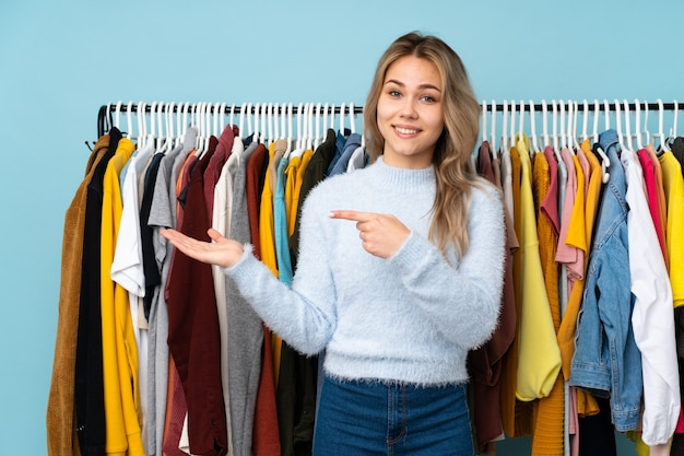 Teenager russian girl buying some clothes on blue holding copyspace imaginary on the palm to insert an ad