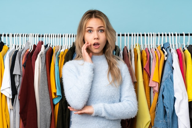 Teenager russian girl buying some clothes isolated on blue