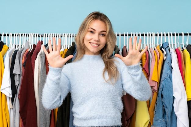 Русская девушка-подросток покупает одежду на синем, считая десять пальцами