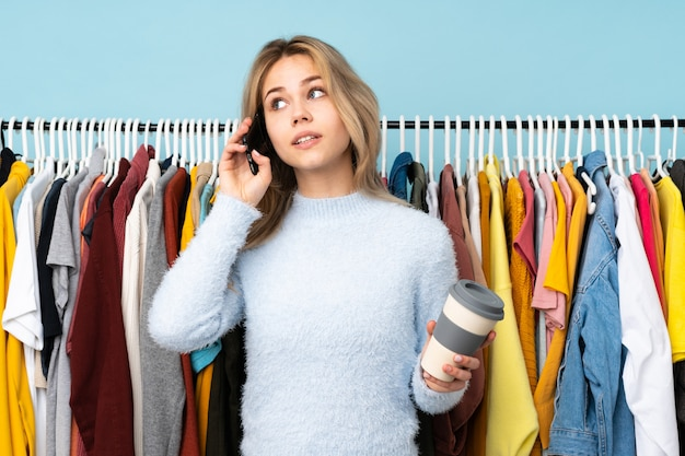 Русская девушка подростка покупая одежду на голубой стене держа кофе для того чтобы отнять и мобильный телефон