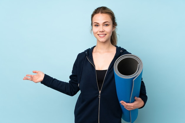 Teenager russian girl holding mat on blue wall extending hands to the side for inviting to come