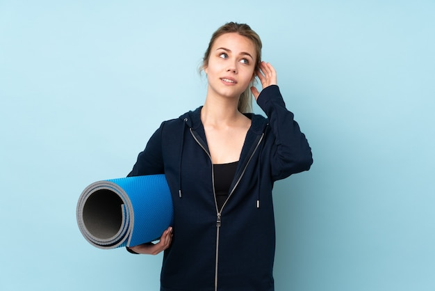 Teenager russian girl holding mat isolated on blue thinking an idea