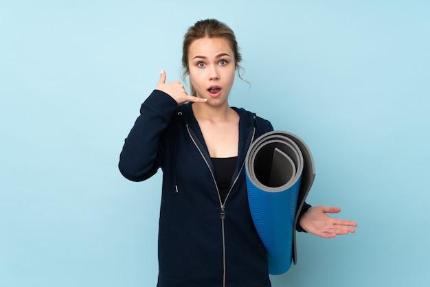 電話のジェスチャーをし、疑う青で隔離のマットを保持している10代のロシアの女の子