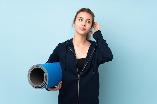 Русская девочка-подросток держит циновку, изолированную на синем, думая об идее