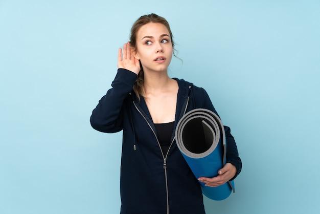 Русская девушка-подросток держит циновку, изолированную на синей стене, слушая что-то, положив руку на ухо