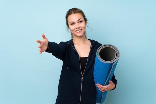 青い壁に隔離されたマットを保持しているティーンエイジャーのロシアの女の子が手で来るように提示し、招待します