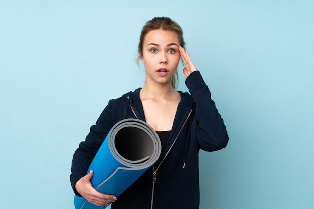 Русская девушка-подросток держит циновку, изолированную на синем, с удивлением и шокированным выражением лица