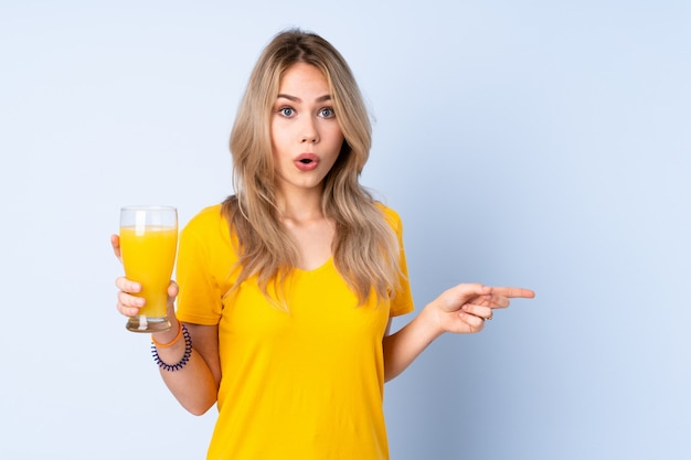Teenager russian girl holding an orange juice on blue wall surprised and pointing side