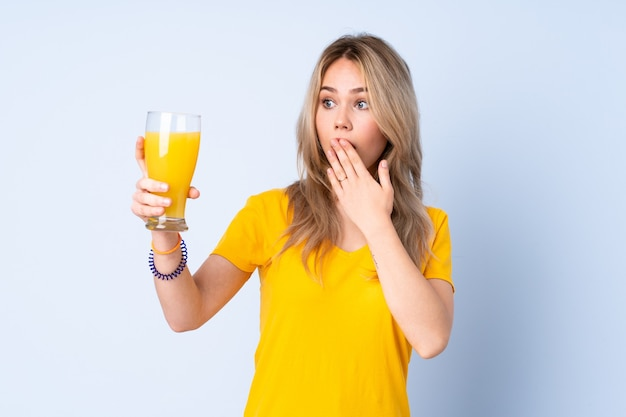 Teenager russian girl holding an orange juice isolated on blue with surprise and shocked facial expression