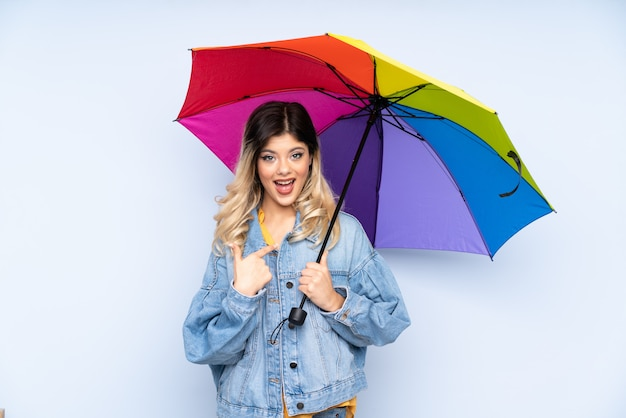 Teenager russian girl holding an umbrella isolated on blue wall with surprise facial expression