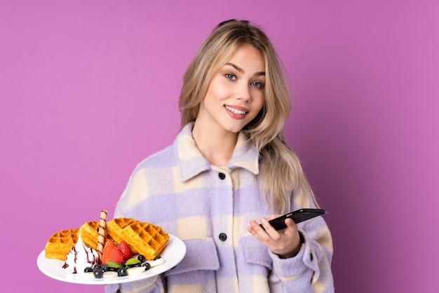 持ち帰り用のコーヒーと携帯電話を保持している紫色に分離されたワッフルを保持している10代のロシアの女の子