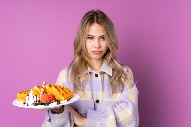 紫に分離されたワッフルを保持している10代のロシアの女の子