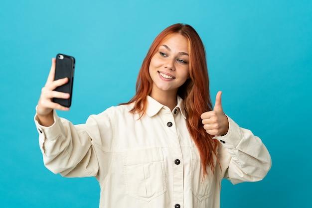 휴대 전화로 셀카를 만드는 파란색 배경에 고립 된 십 대 러시아 소녀