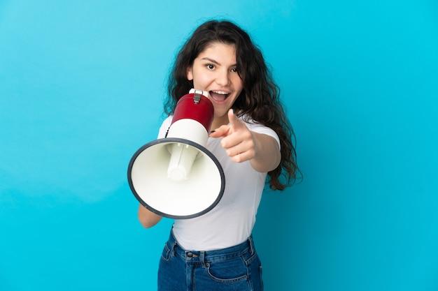 Русская девушка-подросток изолирована на синем фоне, кричит в мегафон, чтобы объявить что-то, указывая на фронт
