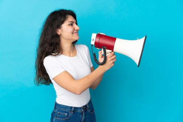 Русская девушка-подросток, изолированные на синем фоне, кричит в мегафон, чтобы что-то объявить