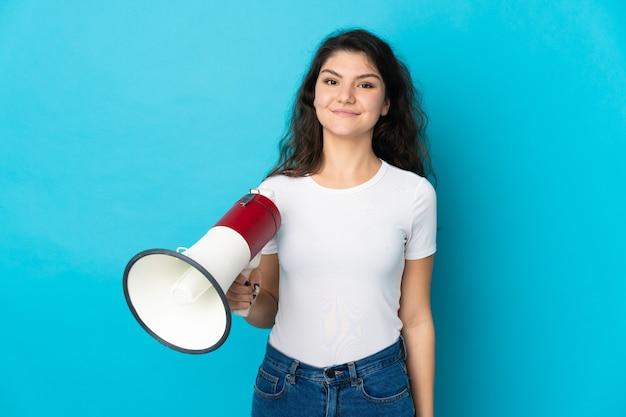 Русская девушка-подросток изолирована на синей стене с мегафоном и много улыбается