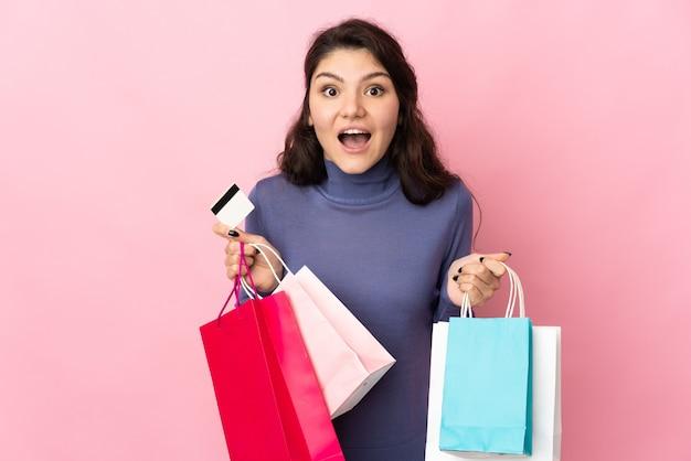 Русская девушка-подросток изолирована на розовом фоне, держа сумки и удивлена
