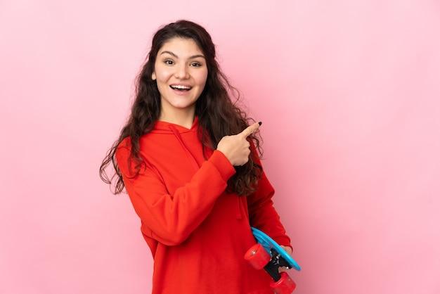 스케이트와 분홍색 배경에 고립 된 측면을 가리키는 십 대 러시아 소녀