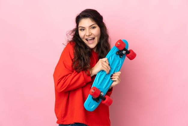 행복 한 표정으로 스케이트와 분홍색 배경에 고립 된 십 대 러시아 소녀