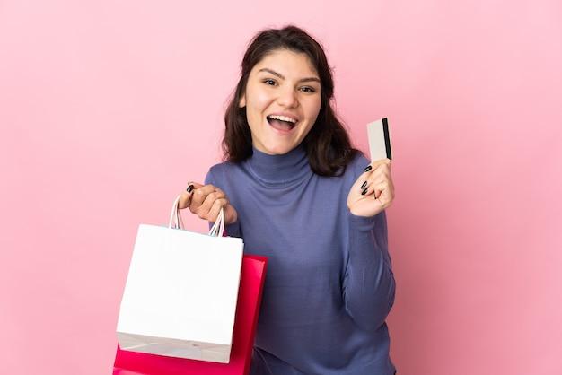Русская девушка-подросток изолирована на розовой стене, держа сумки и кредитную карту