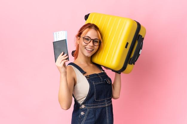 Русская девушка-подросток изолирована на розовой стене в отпуске с чемоданом и паспортом