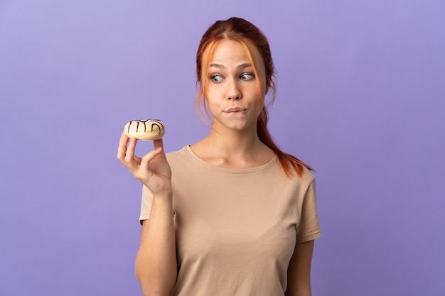 Русская девушка подросток, изолированные на фиолетовом фоне, держа пончик