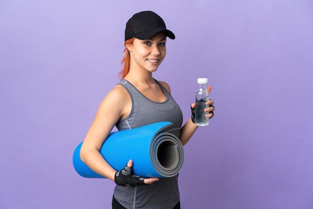 Русская девушка-подросток изолирована на фиолетовом фоне со спортивной бутылкой с водой и с циновкой
