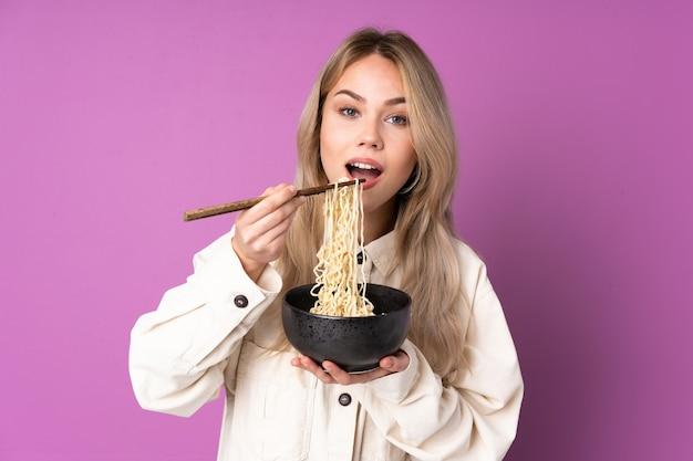 Русская девушка-подросток изолирована на фиолетовой стене, держа миску лапши с палочками для еды и ест ее
