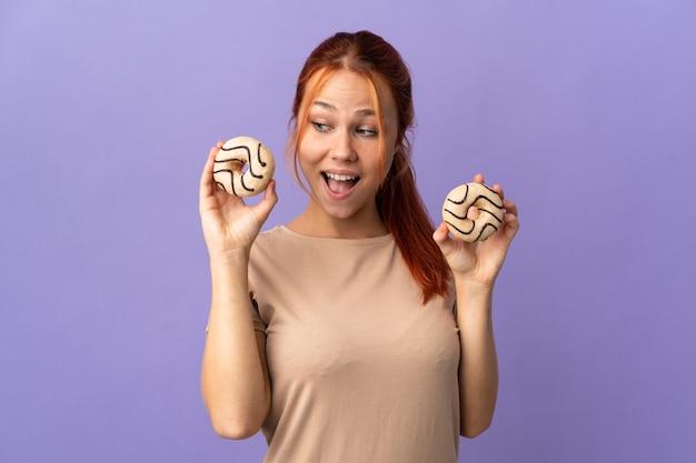 ドーナツを保持し、驚いた紫色の壁に分離された10代のロシアの女の子