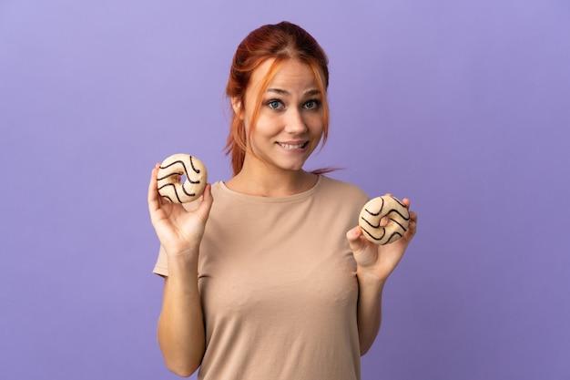 ドーナツを保持している紫色の壁に分離された10代のロシアの女の子