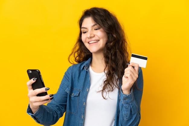 Русская девушка-подросток изолирована на желтом фоне, покупая с мобильного с помощью кредитной карты