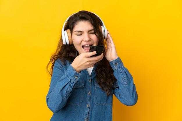 Русская девушка-подросток изолирована на желтом фоне, слушает музыку с мобильного телефона и поет