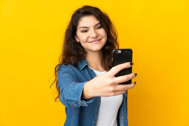 Русская девушка подросток, изолированные на желтом фоне, делая селфи с мобильным телефоном