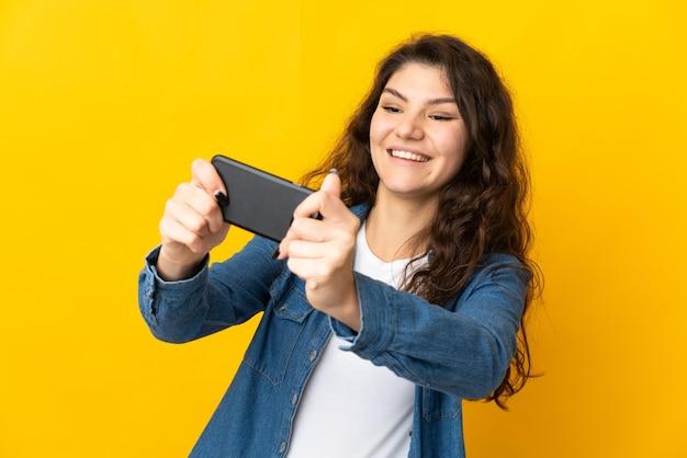 Русская девушка подросток, изолированные на желтом фоне, играя с мобильным телефоном