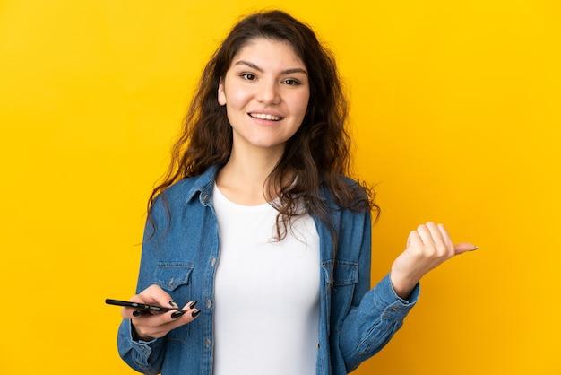 携帯電話を使用して、側面を指して黄色の背景に分離された10代のロシアの女の子
